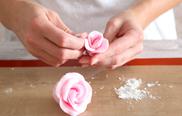6. Fingerspitzen in etwas Stärke tauchen und die Blütenblätter zu einer Rosenform modellieren. Aus dem übrigen Fondant weitere Rosen formen.