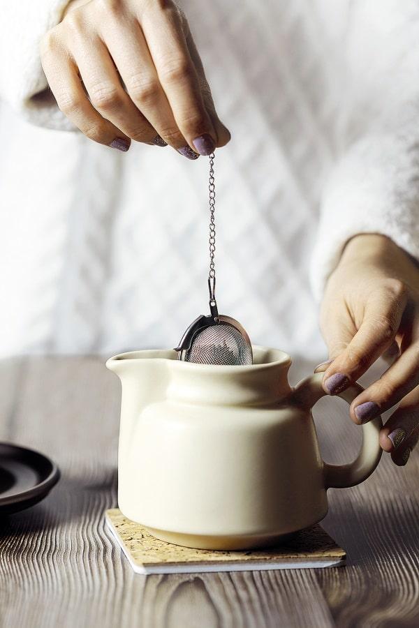 Frau holt Teesieb aus der Kanne