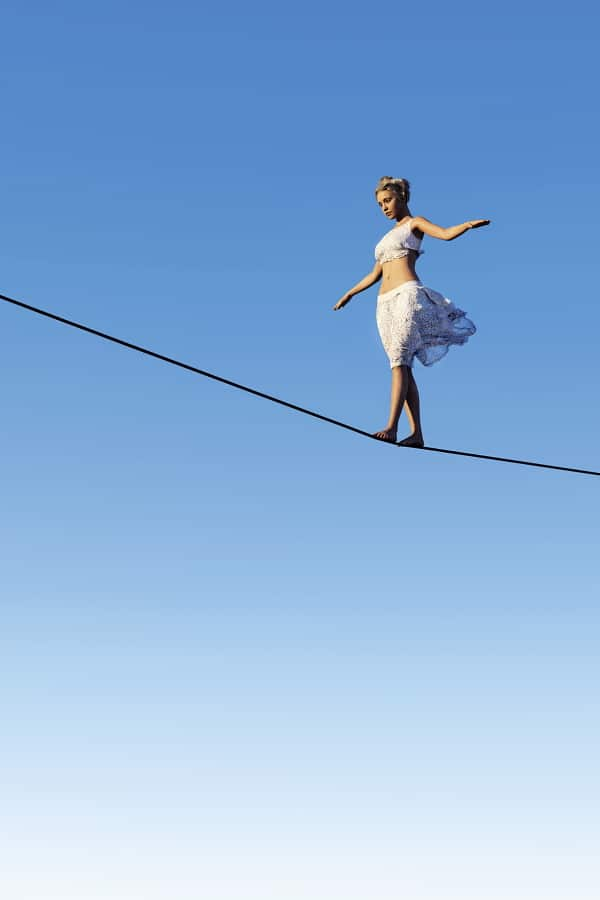 Frau balanciert auf Seil im Himmel