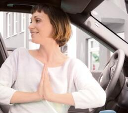 Frau macht Yoga im Auto