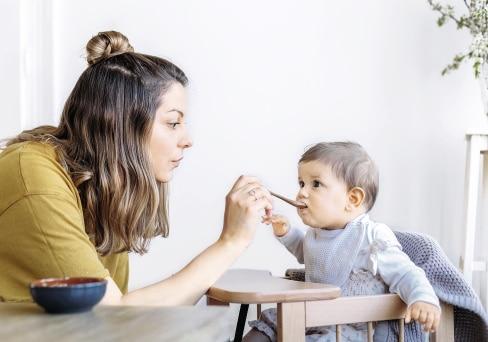 Baby wird mit Brei von Mutter gefüttert