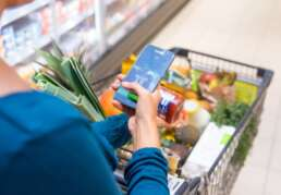 Frau checkt Zutatenliste mit-Smartphone-App beim Einkaufen