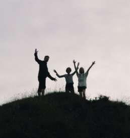 Vater und zwei Kinder erklimmen Berggipfel