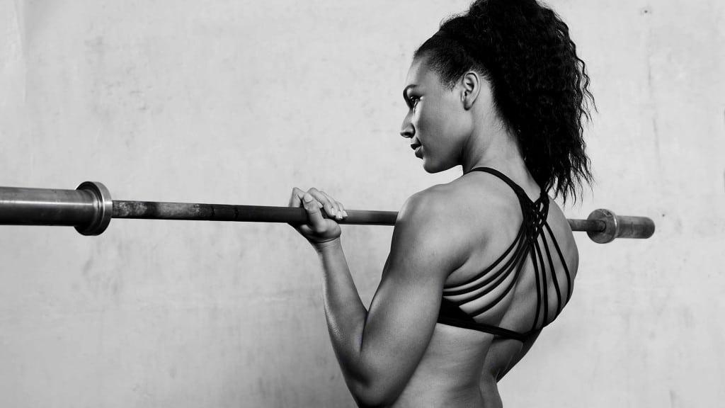 Fitnesscoach umfasst Stange mit Gewichten