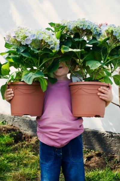 Kind mit Blumentöpfen