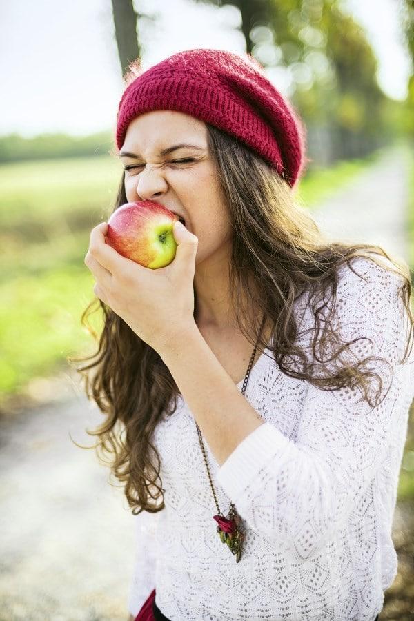 Frau beißt von Apfel
