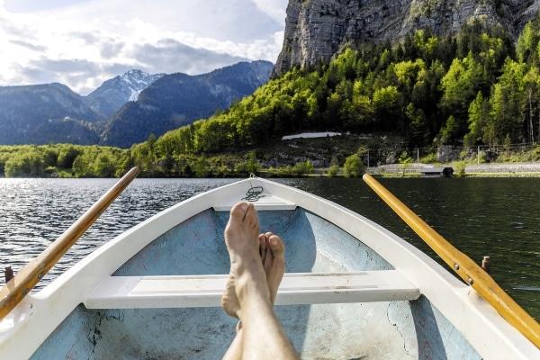 Füße im Boot vor Bergen