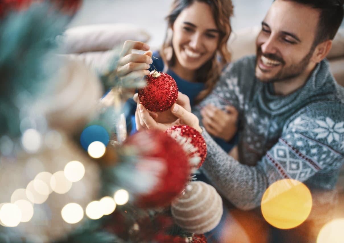 Mann und Frau schmücken Weihnachtsbaum