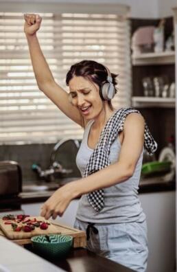 Frau mit Kopfhoerern kocht leidenschaftlich