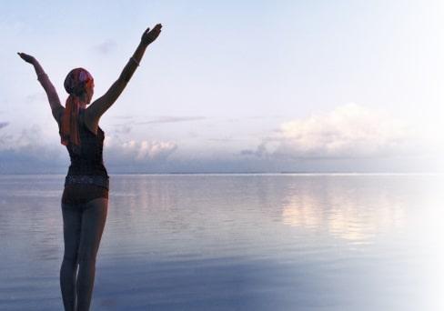 Frau steht am Wasser