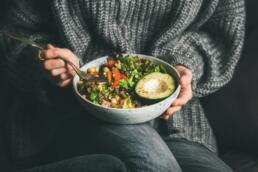Frau hält Schüssel mit gesundem Essen