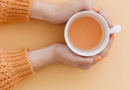 Hände halten Tasse