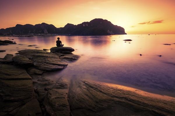 Mann macht Yoga bei Sonnenuntergang