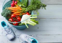 Laufschuh neben Korb voller Gemüse