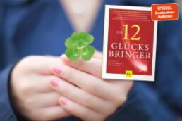 Frau hält 4-blättriges Kleeblatt in der Hand + Cover 12 Glücksbringer