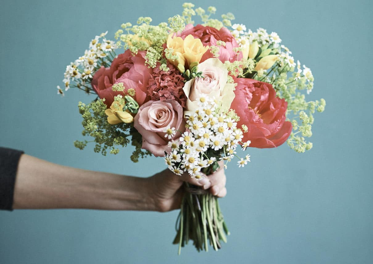 Hand hält Blumenstrauß
