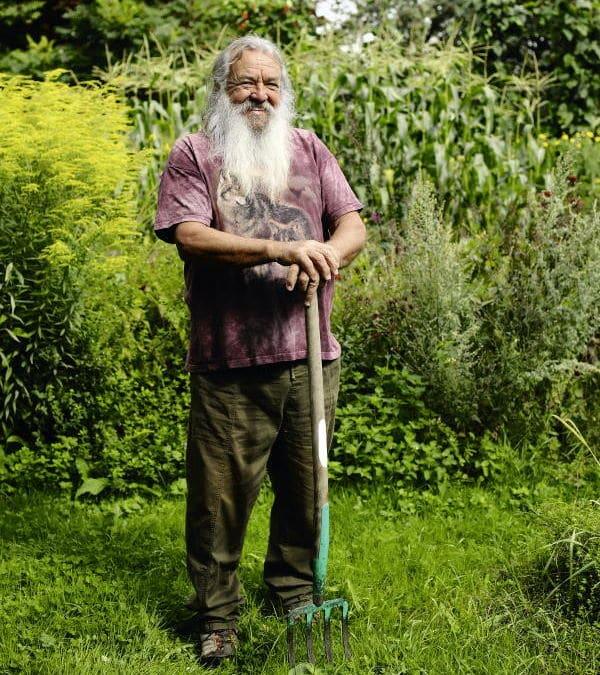 Wolf-Dieter Storl steht mit Spatengabel im Garten