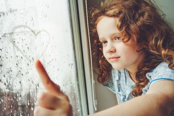 Glückliches Mädchen malt Herz an Fensterscheibe
