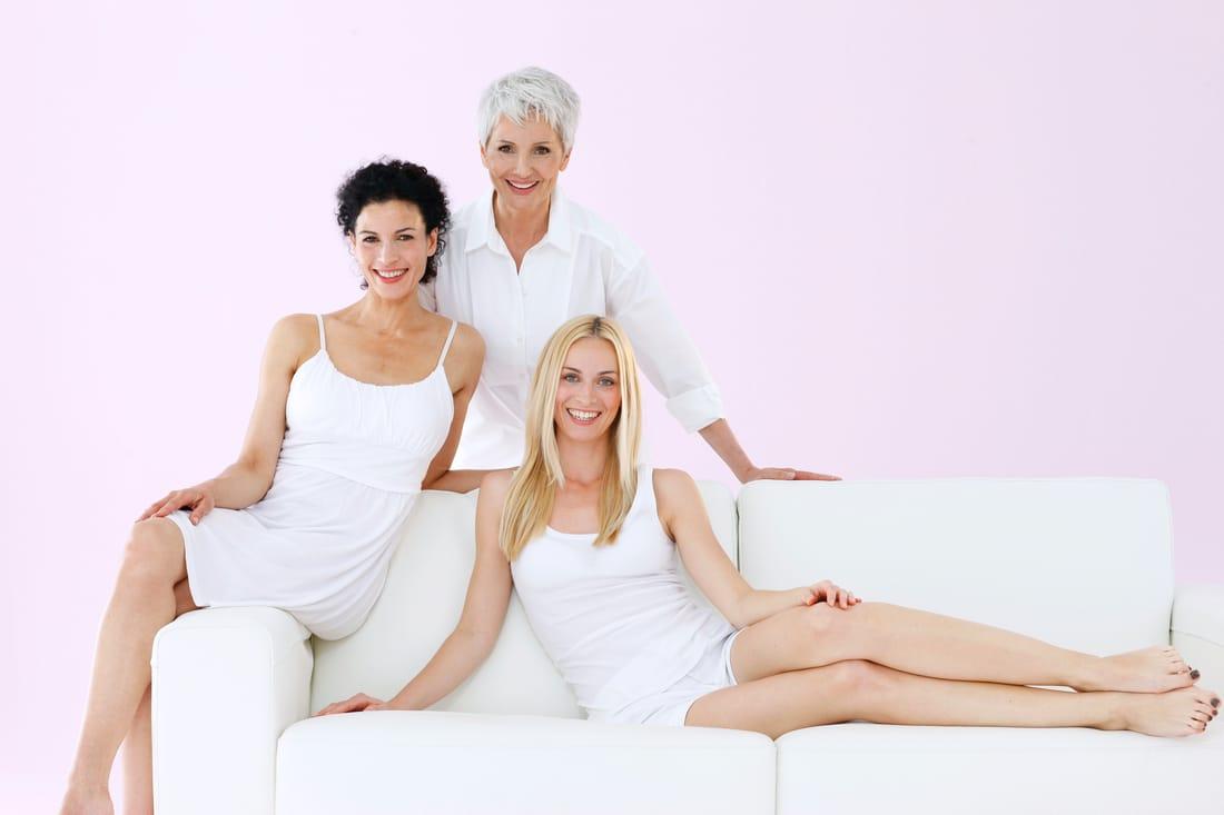 Drei Frauen auf Sofa in Weiß, lachen