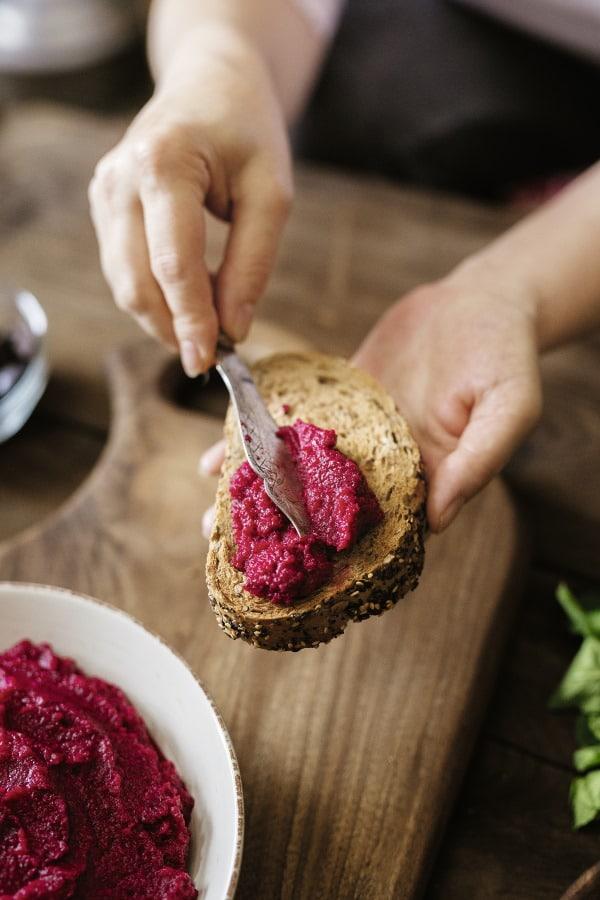 Hand bestriecht Brot mit Rote-Beete-Aufstrich